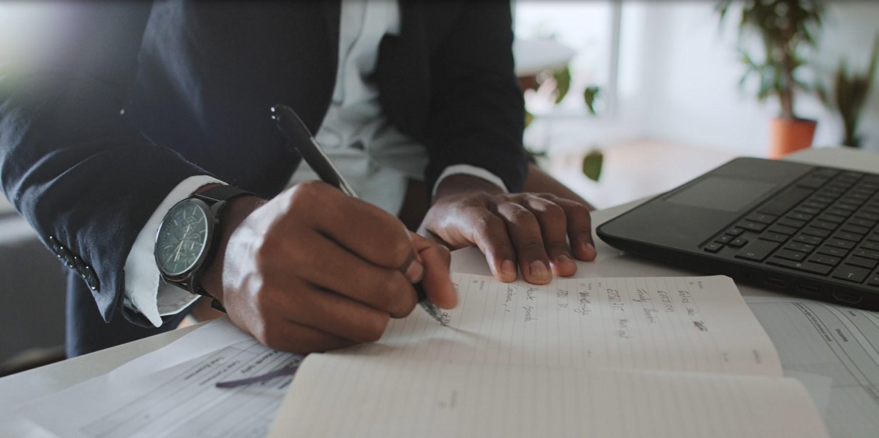 Black businessman making notes at home