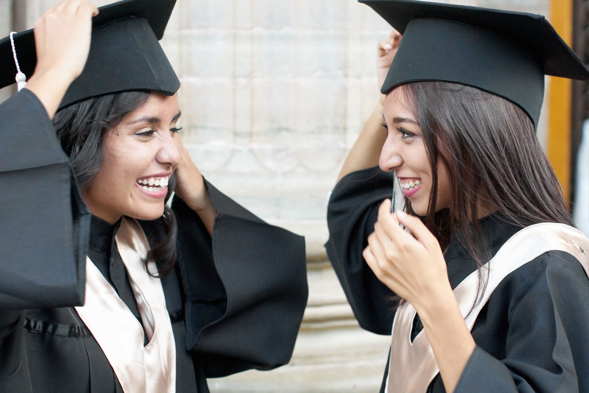 Two young women in graduation cap and gown