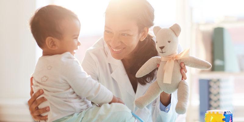 Doctor charms an infant with a teddy bear