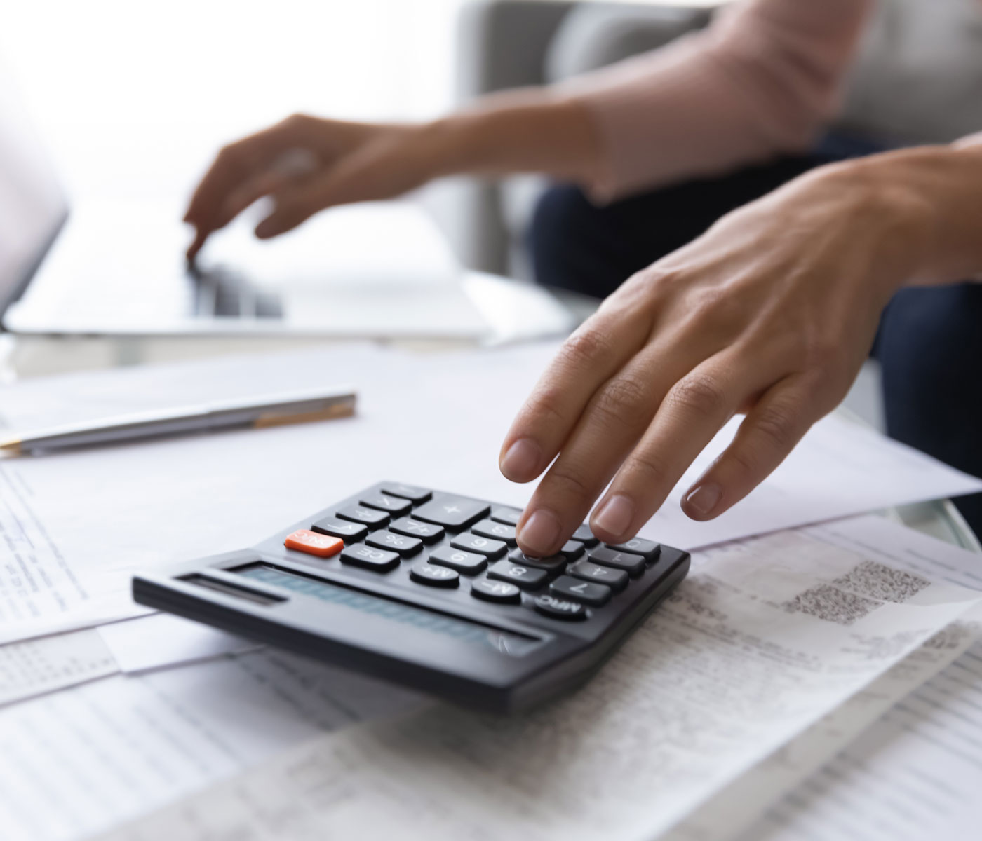 A person adding up donations on a calculator