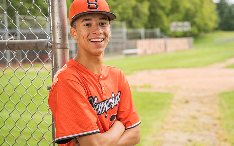 Teenager in Baseball Uniform Smiling