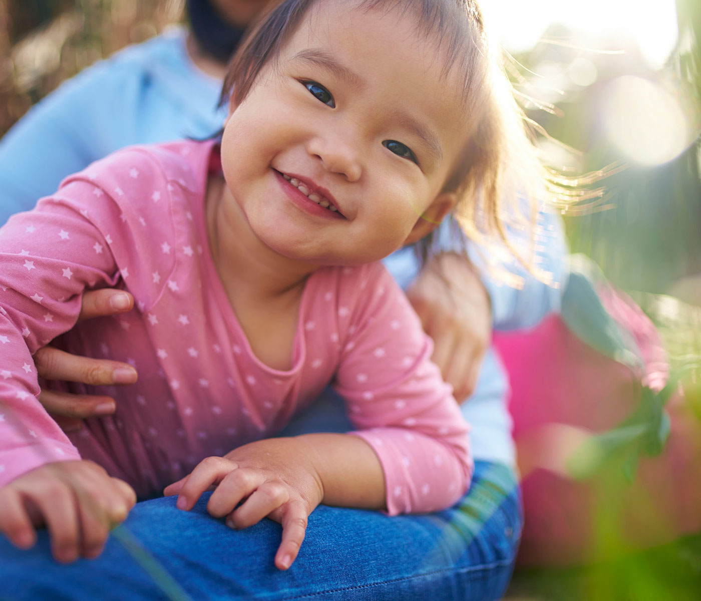 Child Smiling in Parent's Lap with Sun Shining Behind Them