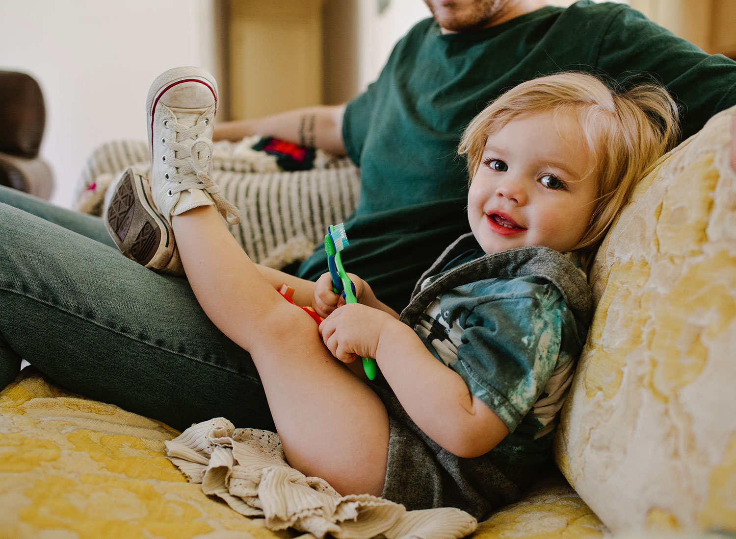 Smiling Child on Couch Holding Toothbrush