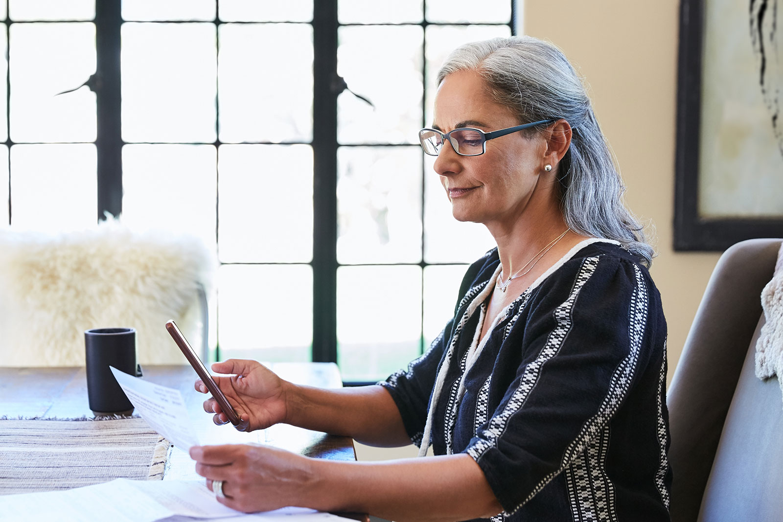 Mature Woman Sitting at Table with Paperwork