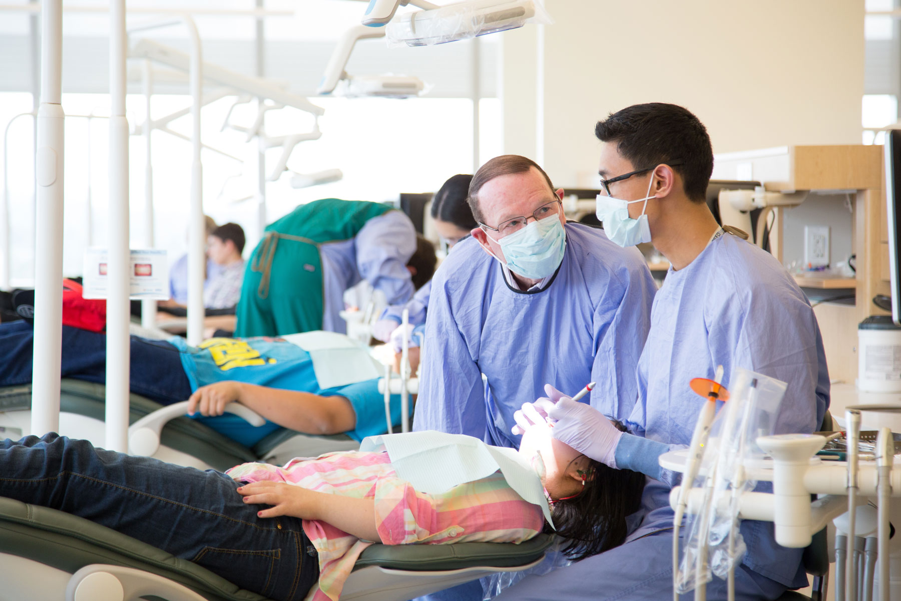 School of Dentistry student consults with faculty member while treating a young patient