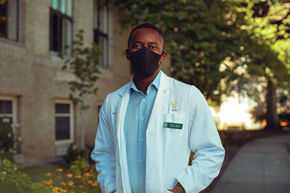 Daniel stands with a mask outside an OHSU building