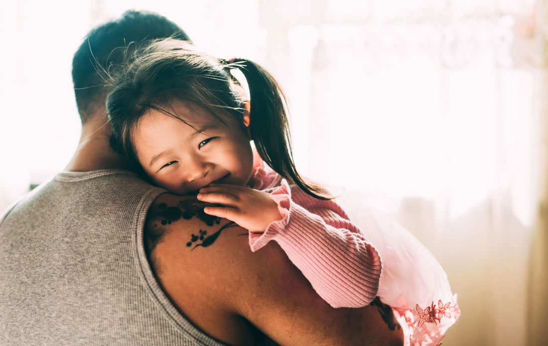 Asian toddler smiles over her father's shoulder