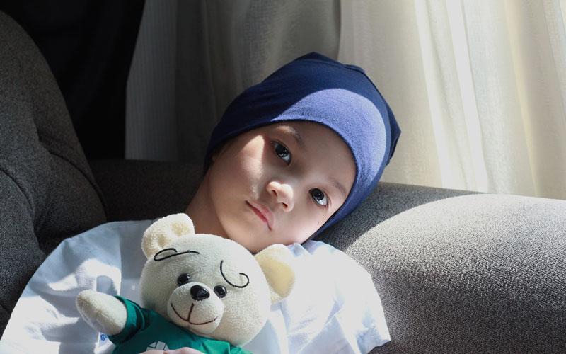Sad child holding teddy bear